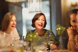 Laughing women friends dining and talking at restaurant tableの写真素材 [FYI02700397]