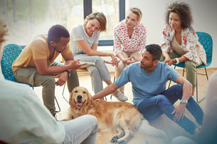 People petting dog in group therapy sessionの写真素材 [FYI02700417]