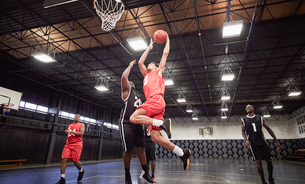 Young male basketball players playing basketball on court in gymnasiumの写真素材 [FYI02700431]