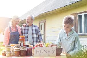 Grandparents and grandson selling honeyの写真素材 [FYI02700433]