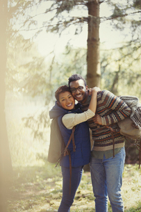 Portrait smiling couple with backpacks hiking in woodsの写真素材 [FYI02700445]