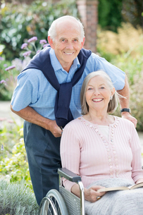 Older man pushing wife in wheelchair outdoorsの写真素材 [FYI02700462]
