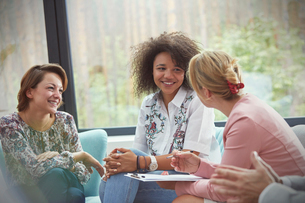 Smiling women talking in group therapy sessionの写真素材 [FYI02700481]