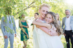 Bride embracing bridesmaid at wedding reception in domestic gardenの写真素材 [FYI02700499]
