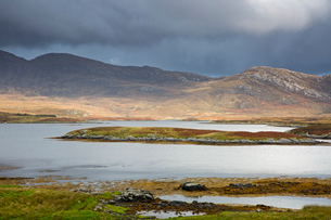 Clouds over craggy hills and lake, Loch Aineort, South Uist, Outer Hebridesの写真素材 [FYI02700519]