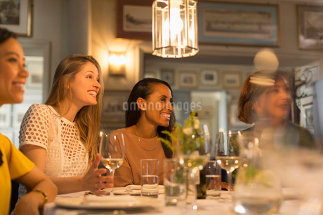Smiling women friends looking away dining and drinking white wine at restaurant tableの写真素材 [FYI02700527]