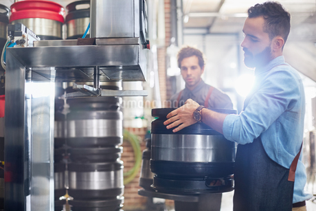 Male brewers filling kegs in breweryの写真素材 [FYI02700528]