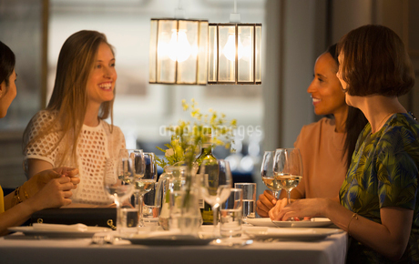 Smiling women friends dining and drinking wine at restaurant tableの写真素材 [FYI02700546]