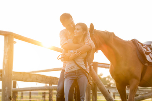 Couple with horse hugging in sunny rural pastureの写真素材 [FYI02700569]