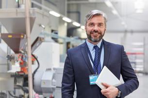 Portrait smiling, confident businessman with digital tablet in fiber optics factoryの写真素材 [FYI02700573]