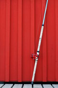Sweden, Bohuslan, Tjorn, fishing rod in front of red wallの写真素材 [FYI02700582]