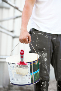 Sweden, Vastra Gotaland, Man carrying bucket with brushの写真素材 [FYI02700599]