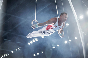 Male gymnast performing on gymnastics rings in arenaの写真素材 [FYI02700602]