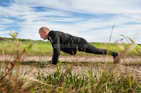 Sweden, Halland, Steninge, Mid-adult man doing push-upsの写真素材 [FYI02700607]