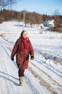 Sweden, Vastergotland, Tarby, Senior woman walking along snoの写真素材 [FYI02700636]