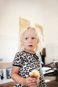 Sweden, Portrait of blond girl (4-5) eating sweet bunの写真素材 [FYI02700678]