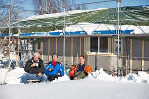 Sweden, Bohuslan, Tjorn, Three men sitting in front of buildの写真素材 [FYI02700684]