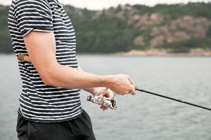 Sweden, Bohuslan, Tjorn, Mid section of young man fishingの写真素材 [FYI02700685]