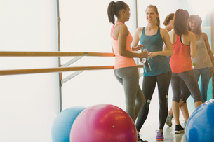 Smiling women talking and drinking water at barre in exercise class gym studioの写真素材 [FYI02700693]