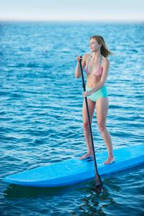 Young woman in bikini paddleboarding on summer oceanの写真素材 [FYI02700698]