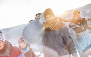 Portrait smiling snowboarder friends carrying snowboardsの写真素材 [FYI02700700]