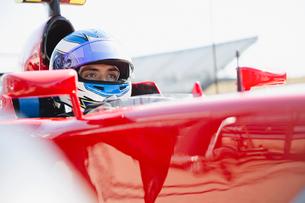 Focused formula one race car driver wearing helmet, looking awayの写真素材 [FYI02700713]