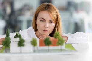 Focused female architect examining modelの写真素材 [FYI02700729]