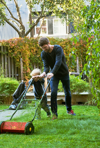 Sweden, Skane, Osterlen, Borrby, Father and son (4-5) mowing lawn in domestic gardenの写真素材 [FYI02700747]
