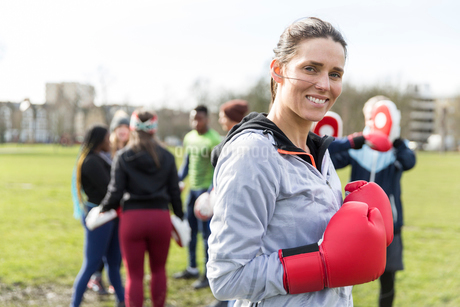 Portrait smiling, confident woman boxing in parkの写真素材 [FYI02700789]