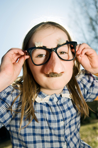 Finland, Kyrkslatt, Portrait of girl (6-7) in funny glassesの写真素材 [FYI02700874]
