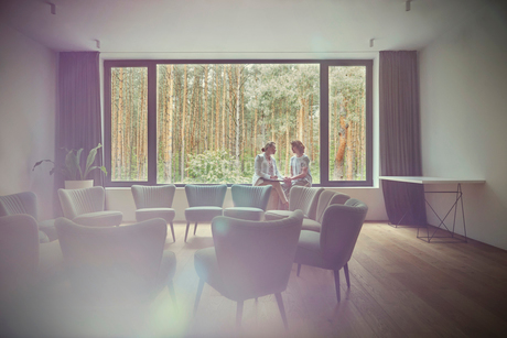 Women talking at window in group therapy roomの写真素材 [FYI02700897]