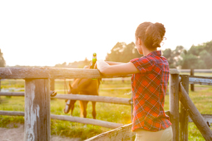Woman drinking beer and watching horse in rural pastureの写真素材 [FYI02700901]