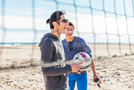 Happy male friends playing beach volleyball on sunny beachの写真素材 [FYI02700942]