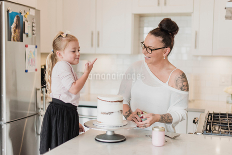 Mother and daughter decorating cake in kitchenの写真素材 [FYI02700945]