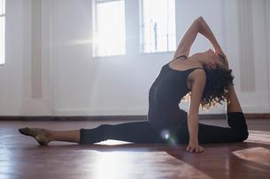 Graceful young female dancer stretching in dance studioの写真素材 [FYI02700955]