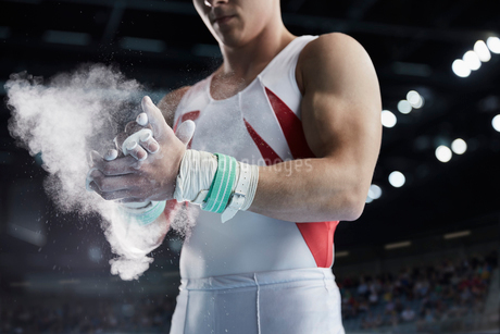 Male gymnast applying chalk powder to handsの写真素材 [FYI02700963]