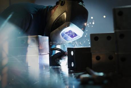 Welder using welding torch on steel in steel factoryの写真素材 [FYI02700971]