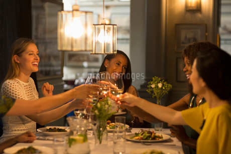 Smiling women friends toasting white wine glasses dining at restaurant tableの写真素材 [FYI02700995]