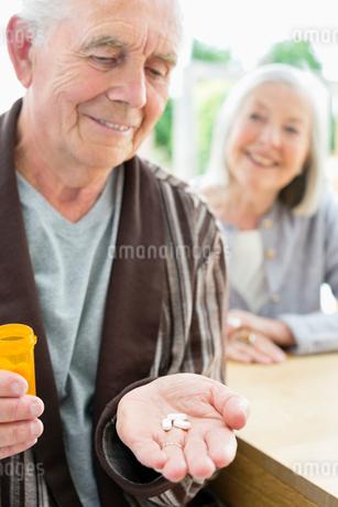 Older man with handful of pillsの写真素材 [FYI02701019]