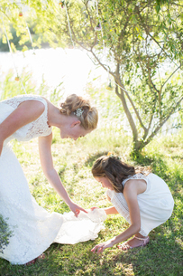 Bride and bridesmaid in domestic garden during wedding receptionの写真素材 [FYI02701029]