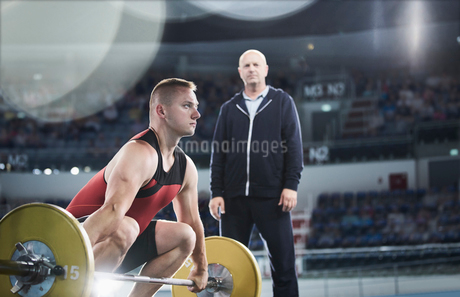 Coach watching focused male weightlifter lifting barbell in arenaの写真素材 [FYI02701067]