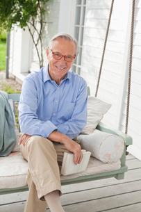 Smiling man sitting on porch swingの写真素材 [FYI02701128]
