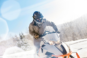 Man riding snowmobile in sunny snowy fieldの写真素材 [FYI02701137]