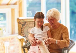 Grandmother teaching granddaughter knittingの写真素材 [FYI02701149]