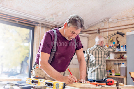 Male carpenter measuring and marking wood plank on workbench in workshopの写真素材 [FYI02701199]