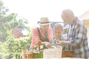 Grandparents and grandson selling honey at farmer's market stallの写真素材 [FYI02701202]