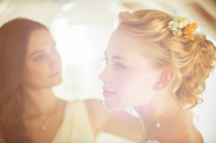 Portrait of bride with bridesmaid in background in domestic roomの写真素材 [FYI02701216]