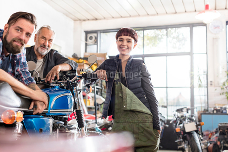 Portrait smiling male and female motorcycle mechanics in workshopの写真素材 [FYI02701230]