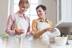 Smiling female caterers baking muffins in kitchenの写真素材 [FYI02701238]