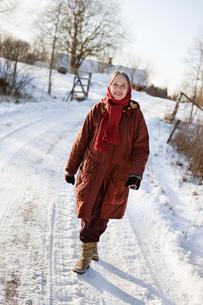 Sweden, Vastergotland, Tarby, Senior woman walking along snoの写真素材 [FYI02701266]
